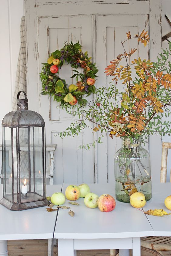 a fall leaf  arrangement, fresh apples, a greenery and apple wreath   all of these decorations are natural