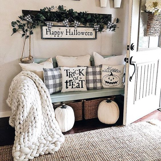 a farmhouse entryway dressed up for Halloween with Halloween pillows, a sign and some dark greenery