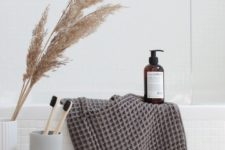 18 a grey towel and a dried grass arrangement and a plywood stool make the bathroom feel like fall