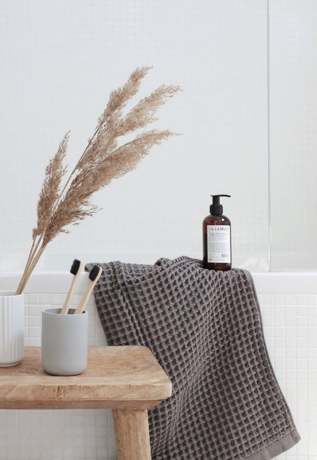a grey towel and a dried grass arrangement and a plywood stool make the bathroom feel like fall