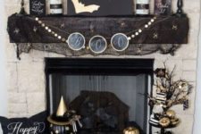 18 a stylish black and gold Halloween mantel with bats, candles, vases with branches, skulls and lots of painted pumpkins is wow