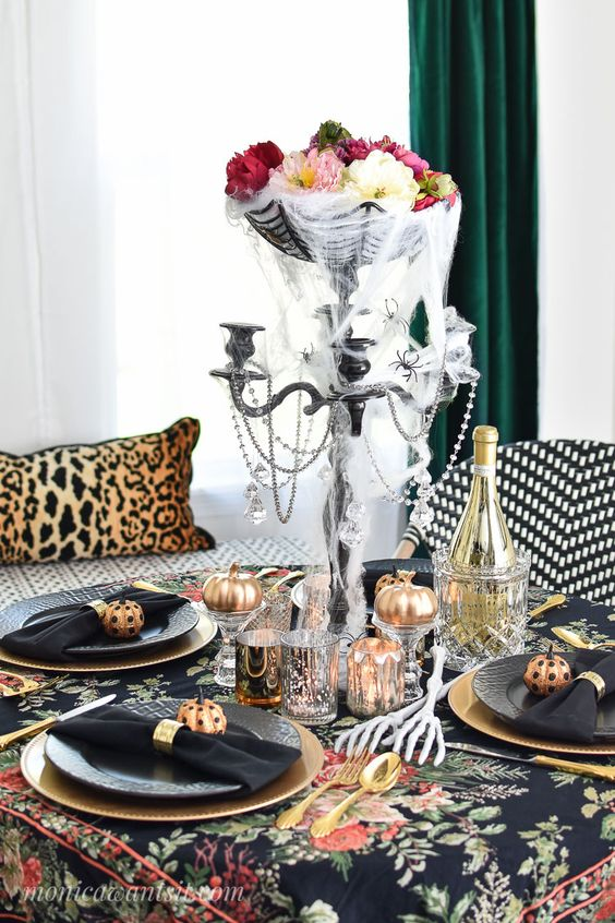 a bold Halloween centerpiece of a black bowl with a spiderweb, beads and some flower heads in the bowl