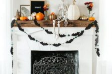 19 a chic and fun Halloween mantel with a skeleton, painted pumpkins, a black bat bunting, black balloon letters and a stylish sign