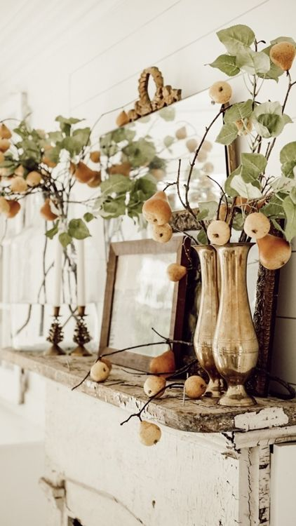 a fall mantel decorated with branches with fresh leaves and pears are amazing and non typical