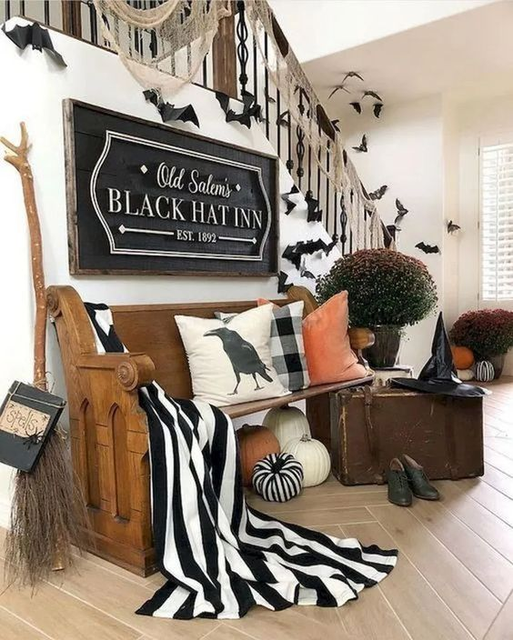 a gorgeous Halloween entryway with large pumpkins, black and white fabric, a witch broom, hat, shoes and some bats