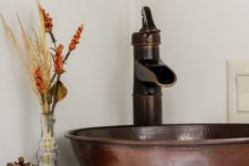 19 a hammered copper sink and faucet, a pumpkin, pinecone and a dried arrangement for pretty fall bathroom decor