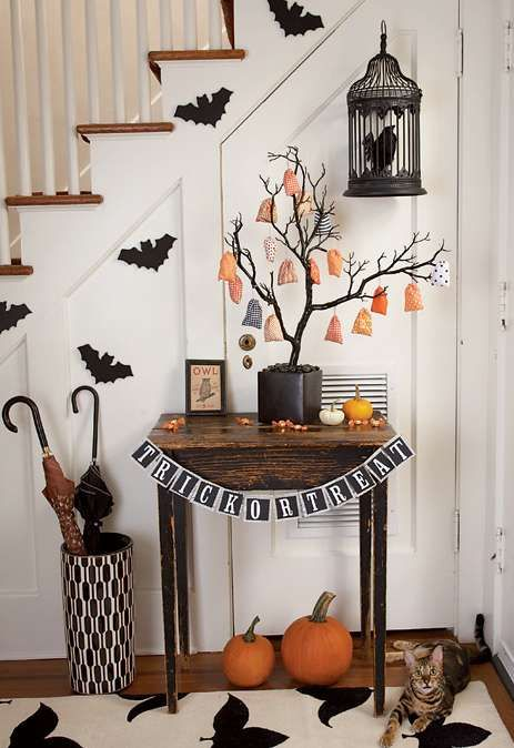 a Halloween entryway with bats, a blackbird in a cage, orange pumpkins, a black and white bunting, a Halloween tree with ornaments