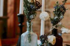 20 a chic Halloween centerpiece of glass bottles with blooms and dried greenery plus some tall candles