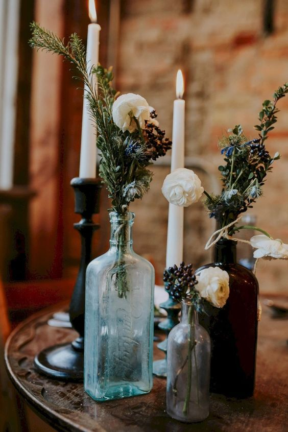 a chic Halloween centerpiece of glass bottles with blooms and dried greenery plus some tall candles