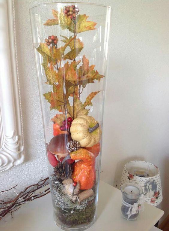 a fall decoration made of a tall vase filled with pinecones, gourds, pumpkins and leaves - all of them are faux