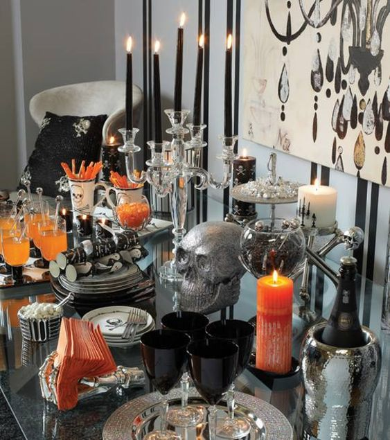 a refined Halloween drink bar with black and white candles, black glasses, touches of orange and sparkly silver details