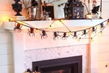 20 a scary Halloween mantel with natural pumpkins, a spider bunting, lights, a house, some busts and branches with leaves