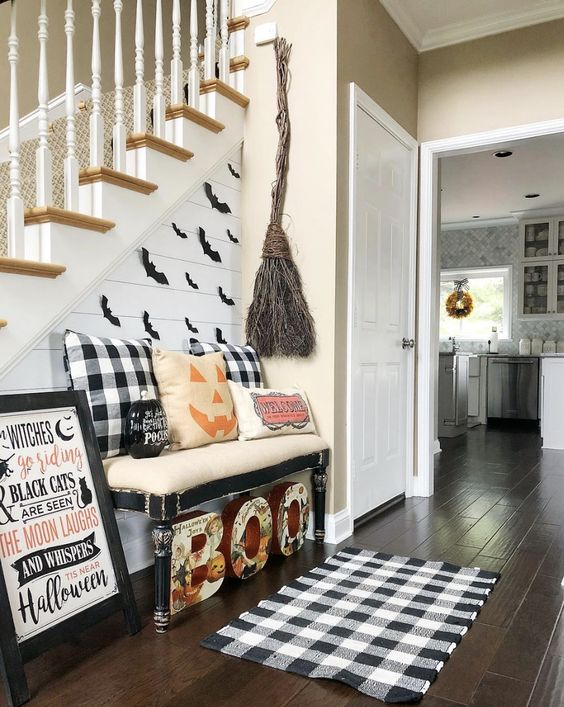 a Halloween entryway with letters, plaid elements, a broom of twigs, a sign and some pumpkin pillows