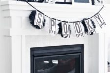 21 a black and white Halloween mantel with a garland, a wreath, a sign, some paper fans, a blackbird and some spiders