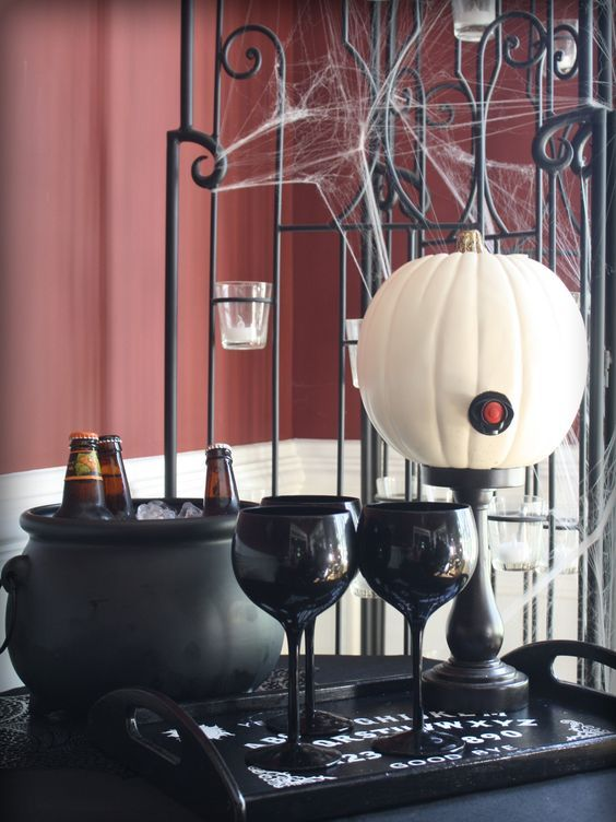a simple drink station with a white pumpkin as a bottle, some black glasses and a cauldron with ice and bottles