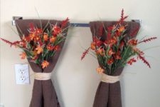 21 an easy and pretty bathroom decoration with brown towels and bright fall blooms attached to them