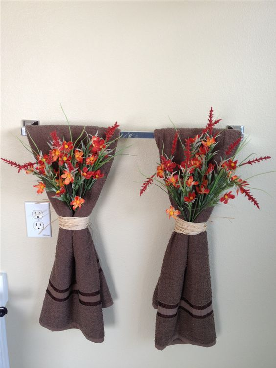 an easy and pretty bathroom decoration with brown towels and bright fall blooms attached to them