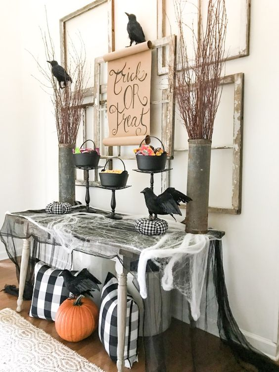a Halloween entryway with spiderweb, checked pillows, a pumpkin, blackbirds, branches in buckets and empty frames