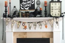 22 a chic Halloween mantel with a bunting, candles, blackbirds and bats, a clock and cages plus a sign on the wall