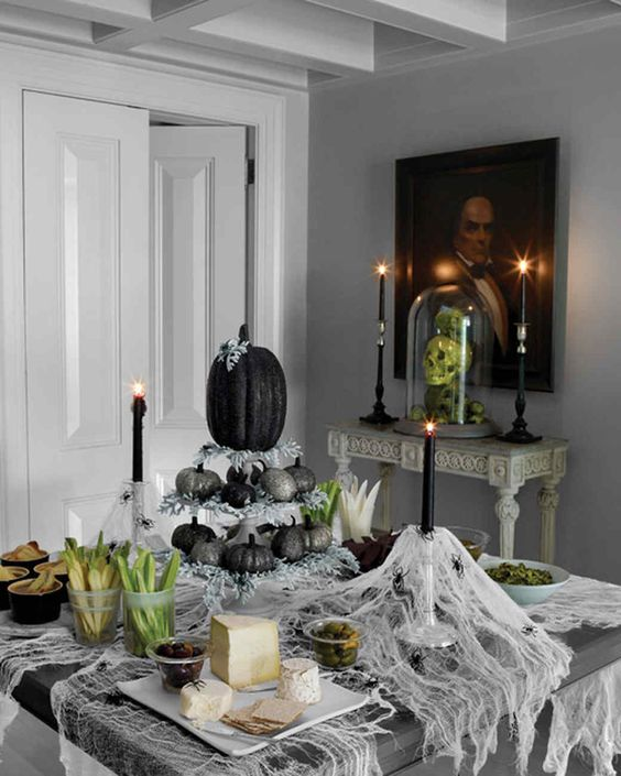 a creative Halloween centerpiece of a stand with glitter silver and black pumpkins plus pale greenery