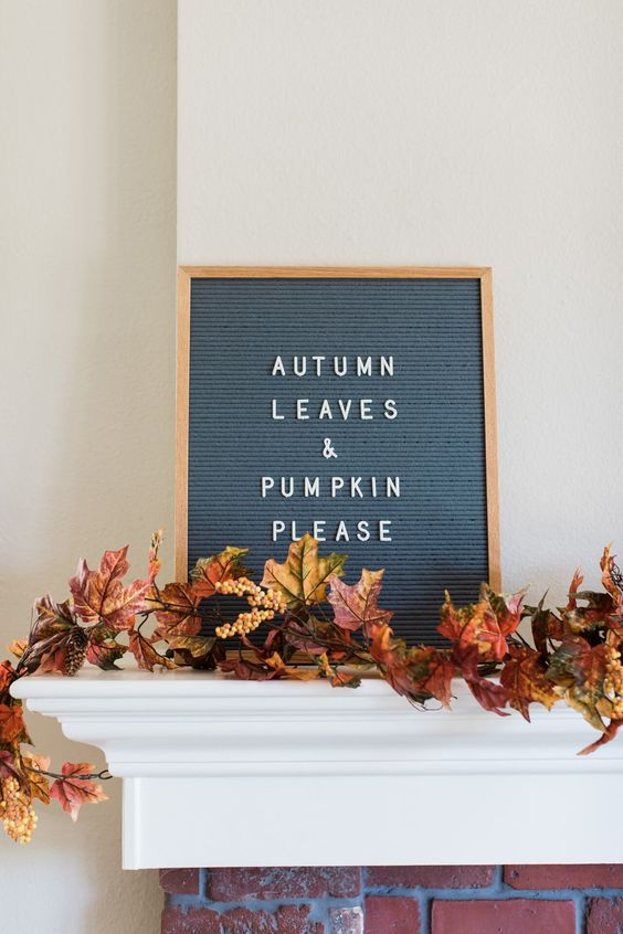 a garland of faux fall elaves with berries is a cool idea to decorate a mantel, a shelf or a window