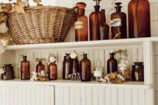 22 bathroom shelves with amber bottles, fall leaves, cotton and dried herbs will brign a fall spirit to the space