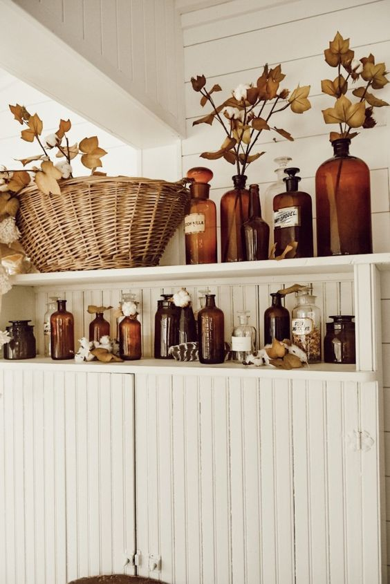 bathroom shelves with amber bottles, fall leaves, cotton and dried herbs will brign a fall spirit to the space