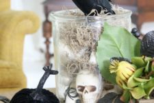 23 a glass jar with hay and skulls, some faux pumpkins, greenery and a blackbird on top for Halloween