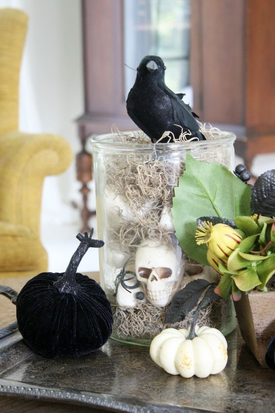 a glass jar with hay and skulls, some faux pumpkins, greenery and a blackbird on top for Halloween