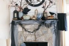23 a haunted Halloween mantel with blackbirds, branches, garlands, a mirror and some pumpkins