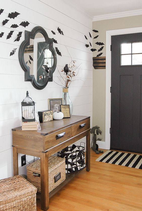 a simple farmhouse Halloween entryway with bats, black and white touches, blackbirds and some white pumpkins