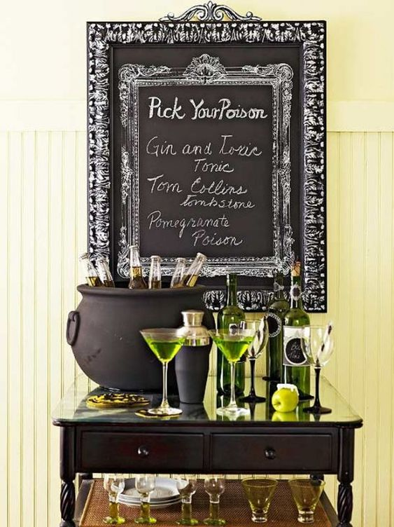 a stylish Halloween drink station with green bottles and sheer glasses, green drinks and a cauldron with bottles plus a sign