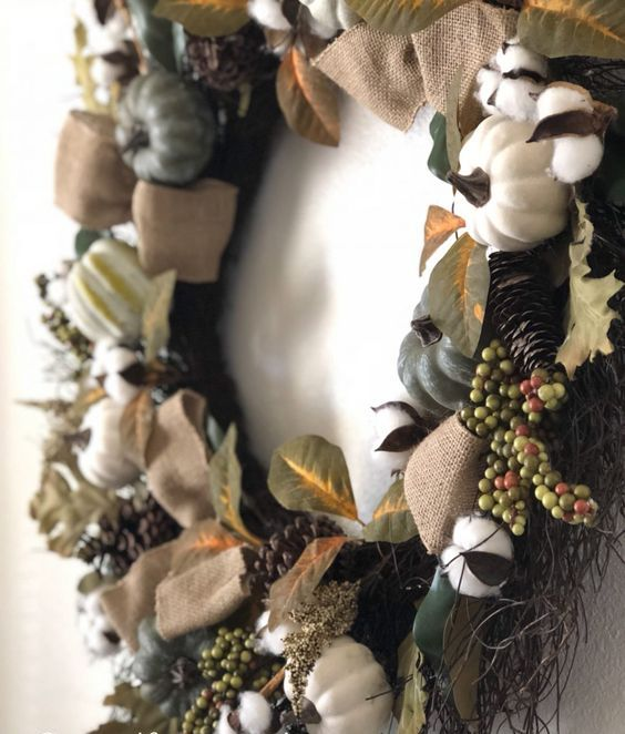 a fall wreath of faux details - pumpkins, gourds, berries, pinecones and cotton, which is dry, will last for long