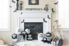 24 a stylish black and white Halloween mantel with bats, painted and stenciled pumpkins, a skull sign and skulls on stands
