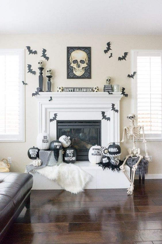 a stylish black and white Halloween mantel with bats, painted and stenciled pumpkins, a skull sign and skulls on stands