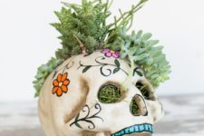 24 a sugar skull filled with grass and succulents is a cool and bright idea for a Day of The Dead party
