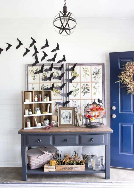 a vintage Halloween entryway with bats, a skull sign and a black cage with a faux blackbird create a mood here