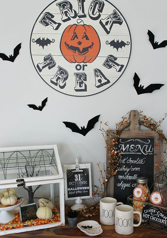 drink station decor with a treat sign, bats, a terrarium with candy corns and pumpkins and a sign plus some berries