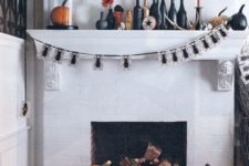 25 a bold Halloween mantel with black and orange candles, black candleholders, black and orange pumpkins, a spider bunting