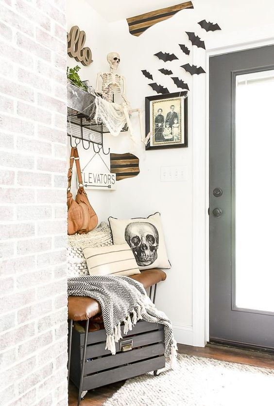 black bats, a skeleton, a skull pillow, a gloomy photo make this small farmhouse entryway Halloween-like