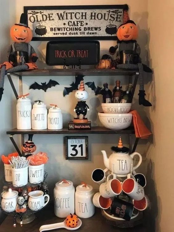 style your hot cocoa bar with black and orange mugs, bats, pumpkin figurines and signs to make it Halloween like