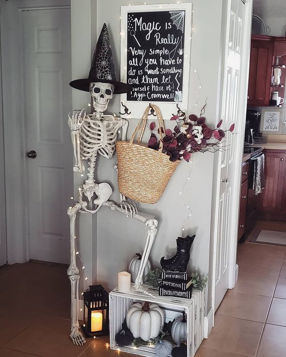 Halloween entryway decor with a skeleton, lights, a candle lantern, a create with pumpkins and a straw bag with dark blooms