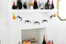 26 a bright Halloween mantel with orange pumpkins, bold black and orange trees, a cage candleholder