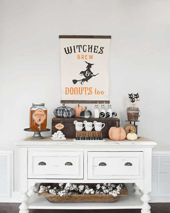 a chic farmhouse Halloween drink station with a sign, fabric pumpkins, witches' brew and some cat toppers