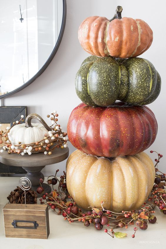 a stack of faux pumpkins placed on a wreath of vines, berries and nuts is a durable fall decoration