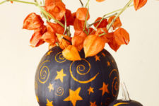 26 painted pumpkins with dried blooms that match will make up a bold and super catchy Halloween centerpiece