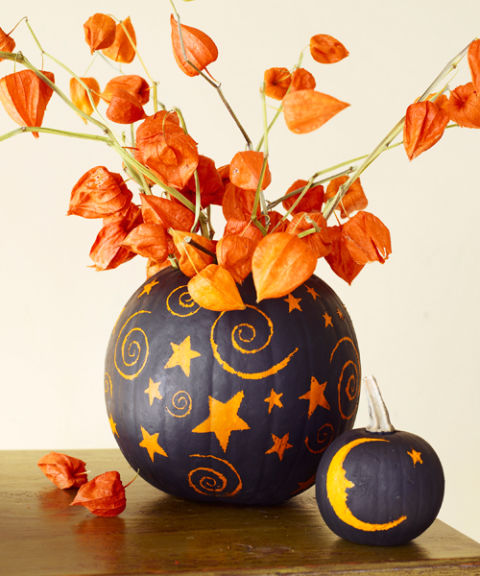 painted pumpkins with dried blooms that match will make up a bold and super catchy Halloween centerpiece
