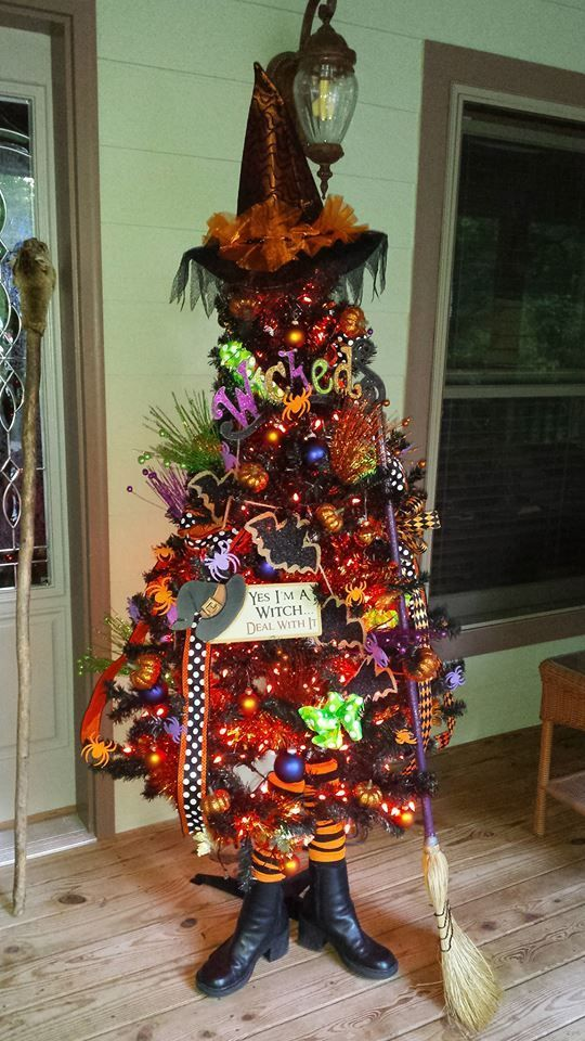 a Halloween tree imitating a witch in a hat, boots and with a broom, with lights, ornaments and hats and letters for fun