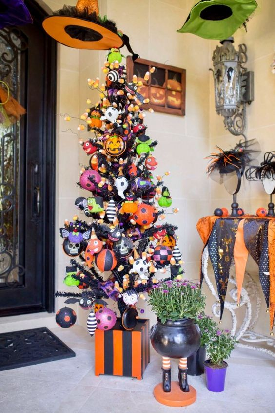 a black Halloween tree decorated in a colorful way, with orange, black and green ornaments, candy corns and ghosts