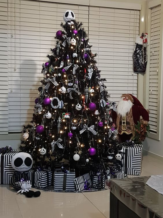 a black Halloween tree decorated with lights, Jack Skellington ornaments, purple ones and some striped bows